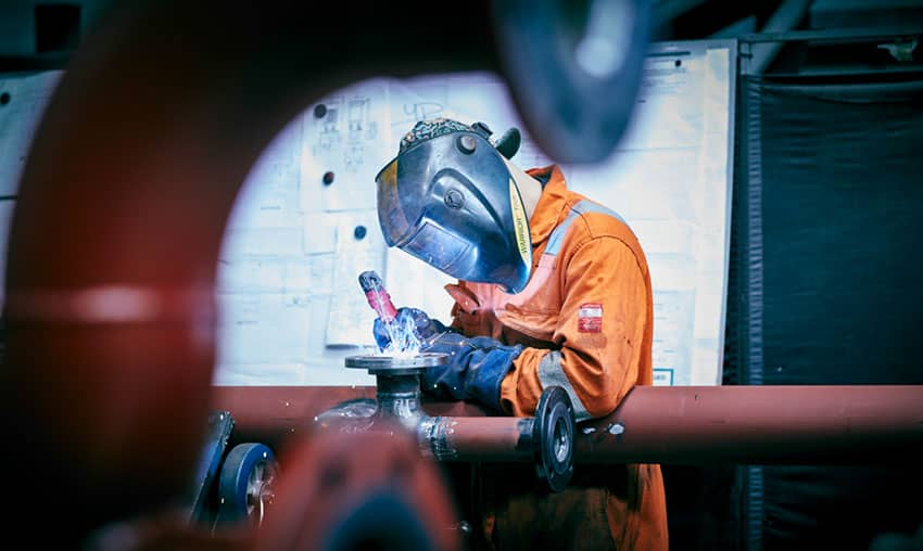 A man welding during the fabrication of a boiler plant room